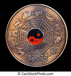Lunar calendar depicted in a bronze medallion with a red and...