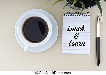 LUNCH AND LEARN text with fountain pen, notepad, and decorative flower on wooden background
