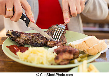 lunch at the cafe, beef steak with mashed potatoes, man`s hands with cutlery