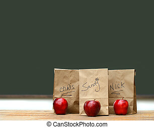 Lunch bags on desk with red apples in front of green...
