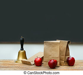 Paper lunch bags with apples and school bell on desk