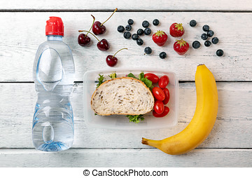 lunch box with fruits and water bottle on white wooden table