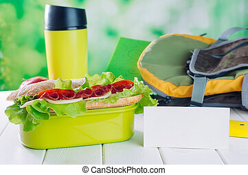 Lunch box with sandwich near card with blank space for text