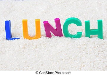 Lunch - word made of colorful plastic letters in the rice