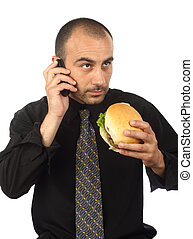 lunch hour - Young businessman eating hamburger, talking by...