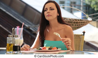 young woman having dinner at a restaurant in downtown