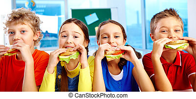 Lunch in school - Four schoolkids looking at camera while...