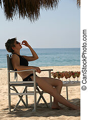 Lunch on the beach - Woman is having shrimp cocktails on the...