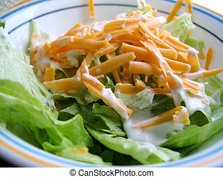 Lettuce with salad dressing and cheddar cheese