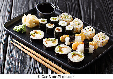 Lunch set Japanese sushi rolls with seafood, vegetables, tofu and tamago closeup on a plate. horizontal