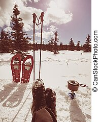 Lunch time during winter trail. Camping on snow and cooking. Red snowshoes