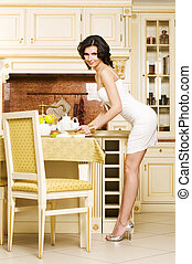 Lunch time - Rich beautiful woman is sitting at her kitchen...