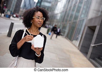 lunch time - young woman eating a take-away in the city