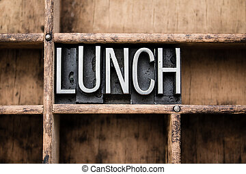 """The word """"LUNCH"""" written in vintage metal letterpress type in a wooden drawer with dividers."""