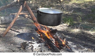 Lunch wanderer. On fire to boil pot of soup for traveler....