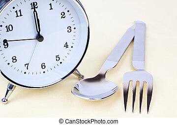 Clock with some silverware on the table