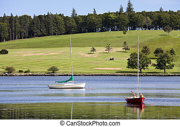 Sailboats in the harbor at Lunenburg, Nova Scotia, Canada with the golf course in the background.