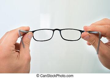 lunettes, tenant mains