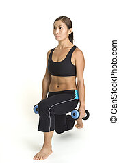 A female fitness instructor demonstrates the finishing position of the lunge with dumbbells