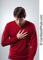 Lungs attack - Young man has a strong lungs pain holding his...