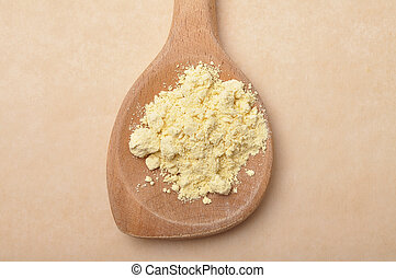 Lupin flour on wooden spoon on brown background