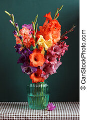 lush bouquet of colored gladioli in a glass vase