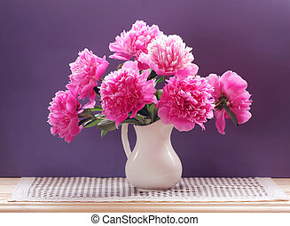 lush bouquet of peonies in a white jug on a purple background.