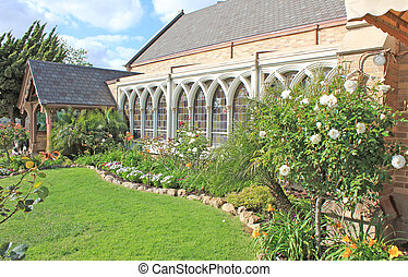 Lush landscape and garden on the side of a house or building.