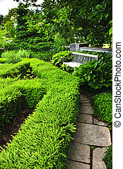 Lush green garden with stone landscaping, hedge, path and ...