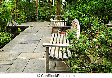 Lush green garden with stone landscaping, pond and benches