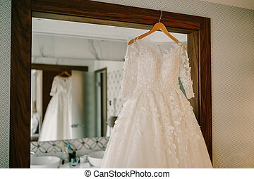 Lush wedding dress on a wooden hanger by the mirror.