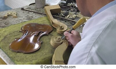 Luthier sculpt a cello head