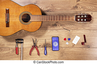 Luthier table top view with classical guitar and tools. Craftsman wooden desk flatlay view with spanish flamenco guitar.