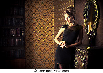 luxurious apartment - Elegant young woman in black evening ...