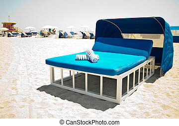 Luxurious beach bed with canopy on a sandy beach