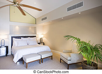 Luxurious double bed bedroom with a wooden fan photographed in daytime light