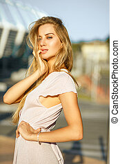 Luxurious blonde girl with long hair posing at the background of street in sun light