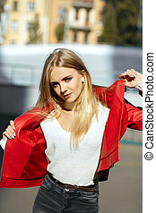 Luxurious blonde model with long hair wearing red leather jacket posing in sun light