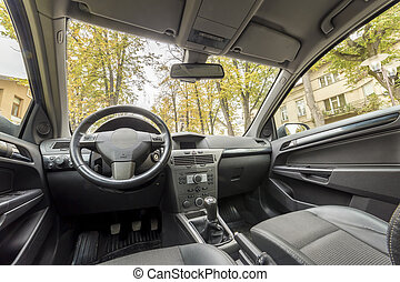 Luxurious car interior. Dashboard, steering wheel, gearshift and comfortable seats. Transportation, design, modern technology concept.
