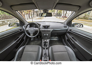 Luxurious car interior details. Comfortable seats, dashboard and steering wheel in soft gray color. Urban view outside. Transportation, design, modern technology, comfortable lifestyle concept.