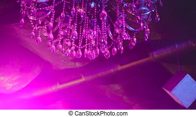 Luxurious chandelier spinning and shining, background in...