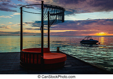 Luxurious deck chair on the background of beautiful colorful sunset over the ocean, Maldives