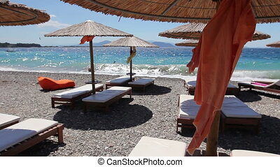 Luxurious fashion loungers, sunbed with umbrella for relaxing by the sandy beach