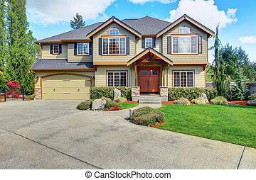 Luxurious American home with well kept lawn and green exterior paint.