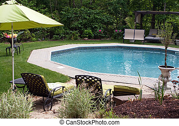 Detail view of a luxurious in ground pool and patio lounge. This partly wooded backyard garden offers the same level of luxury found in many vacation resorts.