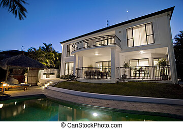 Luxurious mansion exterior at dusk overlooking pool
