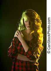 Luxurious model with curly hair in the shadows
