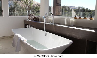 luxurious modern bathroom with bathtub filling