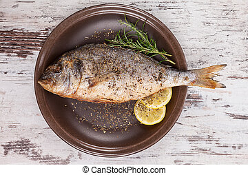 Luxurious seafood. - Grilled fish on brown plate with herbs...