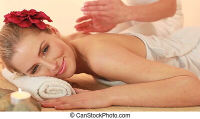 Luxurious Spa Treatment, a glamorous blonde lady with a flower in her hair receives a back pummel massage